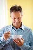 Coppie: Aspetti per mangiare il cereale per la prima colazione Immagine Stock Libera da Diritti