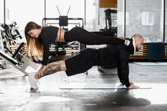 Coppie atletiche che fanno esercizio difficile di sport dove la ragazza sta nella plancia su un uomo che sta nella plancia dentro immagini stock