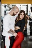 Coppie atletiche felici romantiche L'uomo forte e la bella ragazza snella stanno abbracciando nella palestra moderna accanto allo immagine stock libera da diritti