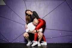 Coppie atletiche sveglie La bella ragazza snella ed il forte uomo atletico in vestiti di sport stanno abbracciando sui precedenti fotografia stock libera da diritti