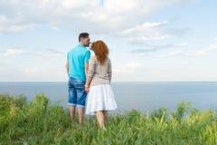 Coppie attraenti che abbracciano e che esaminano lago e cielo blu con le nuvole il tramonto Coppie nell'erba immagini stock libere da diritti