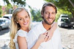 Coppie attraenti che si abbracciano e che sorridono alla macchina fotografica Immagini Stock