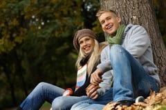 Coppie attraenti che si siedono sulla terra nella sosta di autunno Fotografie Stock Libere da Diritti