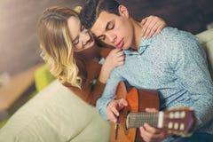 Coppie attraenti che si siedono vicino allo strato con una chitarra Immagini Stock