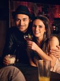 Coppie attraenti che godono delle loro bevande e che sorridono voi Fotografie Stock