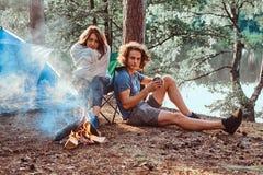 Coppie attraenti dei giovani che raffreddano vicino al falò in foresta soleggiata verde fotografia stock libera da diritti