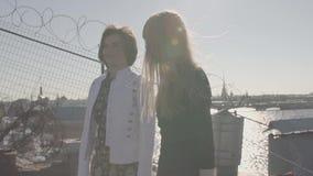 Coppie attraenti delle ragazze sul tetto con la vista scenica del fiume della città archivi video