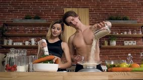 Coppie attraenti di sport che cucinano cena, pranzo nella cucina stock footage