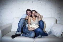 Coppie attraenti divertendosi a casa godere guardando manifestazione di film horror della televisione immagine stock libera da diritti
