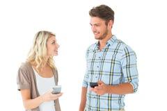 Coppie attraenti facendo uso dei loro smartphones Fotografia Stock Libera da Diritti