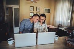Coppie attraenti facendo uso del computer portatile insieme sul sofà da comperare online a fotografia stock