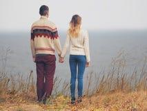 Coppie attraenti giovani in maglioni tricottati che stanno su una scogliera Fotografia Stock