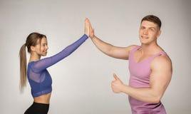 Coppie attraenti sportive in abiti sportivi d'avanguardia che danno l'un l'altro alti cinque immagine stock