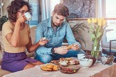 Coppie attraenti, tipo alla moda barbuto bello e ragazza riccia di bellezza mangianti un pasto a casa Immagini Stock
