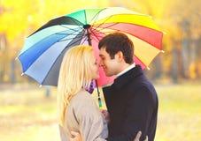 Coppie bacianti romantiche del ritratto nell'amore con l'ombrello variopinto insieme al giorno soleggiato caldo sopra le foglie g fotografie stock libere da diritti