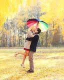 Coppie bacianti romantiche felici nell'amore con l'ombrello variopinto insieme al giorno soleggiato caldo sopra le foglie gialle immagini stock