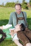 Coppie bavaresi che si siedono nell'erba Fotografia Stock