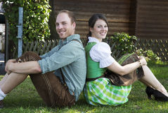 Coppie bavaresi che si siedono nell'erba Immagini Stock