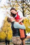 Coppie bavaresi in Tracht nell'abbraccio amoroso con l'adeguamento verso l'alto Fotografia Stock Libera da Diritti