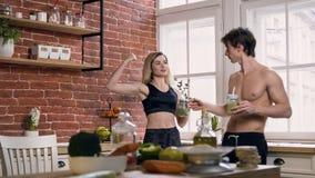 Coppie belle di sport con il frullato in mani che parlano nella cucina stock footage
