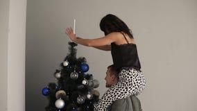 Coppie belle giovani che decorano insieme un albero di Natale La ragazza castana si siede sulle spalle del suo ragazzo e video d archivio