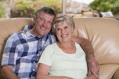 Coppie belle senior di medio evo intorno 70 anni insieme a casa del salone dello strato felice sorridente del sofà che sembra dol Immagini Stock