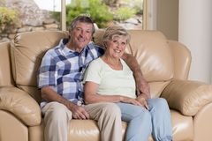 Coppie belle senior di medio evo intorno 70 anni insieme a casa del salone dello strato felice sorridente del sofà che sembra dol Fotografia Stock Libera da Diritti