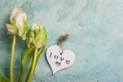 Coppie bianche e verdi del tulipano con cuore di legno Fotografia Stock