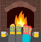 Coppie in calzini caldi che si rilassano vicino al camino Fotografia Stock