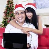 Coppie in cappelli di Santa con un computer portatile Immagini Stock