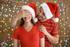 Coppie in cappelli di Santa sul fondo vago delle luci Celebrazione di natale Immagine Stock