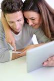 Coppie a casa facendo uso insieme del computer portatile e dello smartphon Fotografie Stock Libere da Diritti