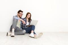 Coppie casuali che comperano online con il computer portatile, colpo dello studio Fotografia Stock Libera da Diritti