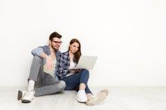 Coppie casuali che comperano online con il computer portatile, colpo dello studio Fotografia Stock