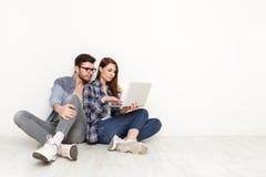 Coppie casuali che lavorano con il computer portatile, colpo dello studio Fotografia Stock