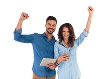 Coppie casuali sorridenti che celebrano mentre tenendo compressa e telefono Immagine Stock Libera da Diritti
