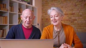 Coppie caucasiche dai capelli grigi senior che commentano il contenuto in computer portatile in ufficio archivi video