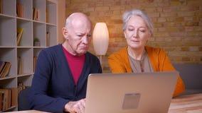 Coppie caucasiche dai capelli grigi senior che discutono allegro contento in computer portatile in ufficio archivi video