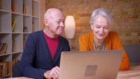 Coppie caucasiche dai capelli grigi senior che parlano felice davanti al computer portatile in ufficio video d archivio