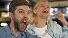 Coppie caucasiche estremamente felici circa il gioco di conquista favorito del gruppo di sport, lega video d archivio