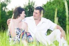 Coppie caucasiche felici che si rilassano insieme all'aperto abbraccio Immagini Stock