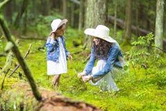 Coppie caucasiche tranquille e positive della madre e di piccola figlia che hanno tempo insieme nella foresta verde di estate immagine stock
