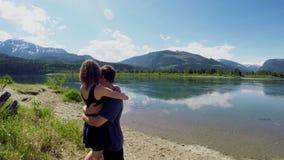 Coppie che abbracciano vicino alla riva del lago 4k archivi video