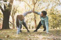 Coppie che allungano nel parco Togethe di lavoro di esercizio delle giovani coppie Fotografia Stock