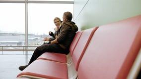 Coppie che aspettano al terminale di aeroporto con i biglietti Fotografie Stock Libere da Diritti