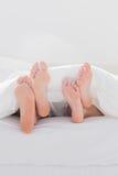 Coppie che attraversano i loro piedi sotto il piumino Fotografia Stock
