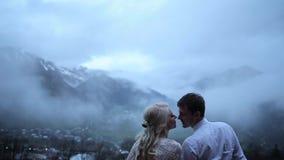 Coppie che baciano sui precedenti delle montagne stock footage