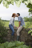 Coppie che baciano sulla parete della campagna Fotografie Stock Libere da Diritti