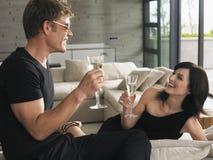 Coppie che bevono Champagne In Living Room Fotografia Stock Libera da Diritti