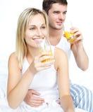 Coppie che bevono il succo di arancia Fotografia Stock Libera da Diritti